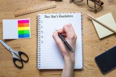 Escritura en la libreta con resoluciones del ` s del Año Nuevo en el top y el li Fotos de archivo libres de regalías