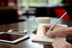Escritura en un cuaderno durante trabajo Fotos de archivo libres de regalías