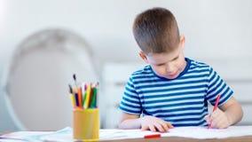 Escritura entusiasta del niño pequeño en el papel usando el lápiz colorido en el tiro medio de la sala de clase almacen de video