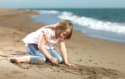 Escritura feliz de la muchacha en la arena Foto de archivo libre de regalías