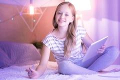Escritura feliz de la muchacha en su cuaderno Fotografía de archivo