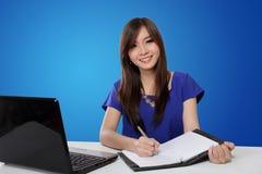 Escritura feliz de la mujer en el cuaderno, en fondo azul Foto de archivo