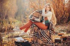 Escritura feliz de la mujer en el parque del otoño fotografía de archivo