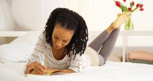Escritura feliz de la mujer negra en diario Fotos de archivo