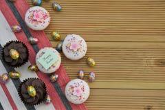 Escritura feliz de Pascua con las decoraciones lindas de las tortas y del huevo de Pascua Imágenes de archivo libres de regalías