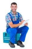 Escritura feliz del fontanero en el tablero mientras que se sienta en la caja de herramientas Fotos de archivo