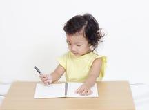 Escritura feliz linda de la niña algo fotos de archivo