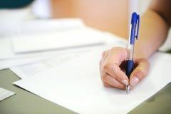 Escritura femenina de la mano en el documento Fotos de archivo