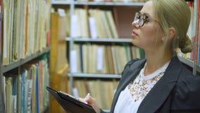 Escritura femenina del bibliotecario en el tablero en la biblioteca almacen de video