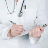 Escritura femenina del doctor en el papel en blanco de la libreta del tablero Imagen de archivo