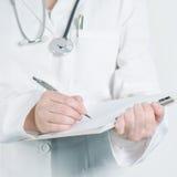 Escritura femenina del doctor en el papel en blanco de la libreta del tablero Fotografía de archivo libre de regalías