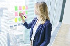 Escritura femenina del empresario en notas pegajosas coloridas sobre la ventana fotografía de archivo