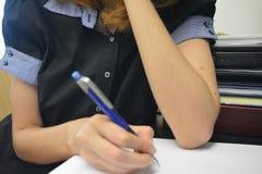 Escritura femenina joven en el papel Imágenes de archivo libres de regalías