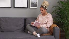 Escritura hermosa de la muchacha en el cuaderno mientras que se sienta en el sofá cómodo en casa almacen de video