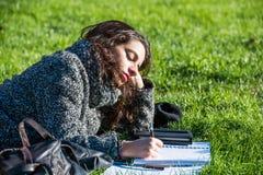 Escritura hermosa de la muchacha en un cuaderno que miente en hierba verde Fotografía de archivo