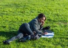 Escritura hermosa de la muchacha en un cuaderno y el hablar en el teléfono Foto de archivo