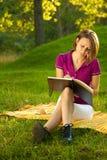 Escritura hermosa de la mujer en su diario en el parque Fotografía de archivo libre de regalías