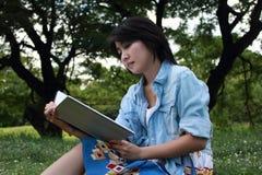 Escritura hermosa de la mujer joven al aire libre en un parque Imágenes de archivo libres de regalías