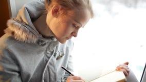 Escritura hermosa joven de la muchacha en su diario y el soñar despierto. metrajes