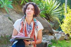 Escritura hermosa joven de la mujer en libro de ejercicio afuera Imagen de archivo libre de regalías