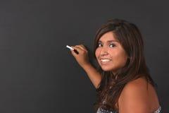 Escritura hispánica del adolescente en una pizarra Fotografía de archivo