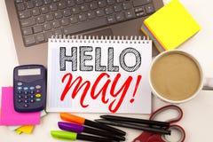 Escritura hola mayo de la palabra Salte en la oficina con el ordenador portátil, marcador, pluma, efectos de escritorio, café Con Foto de archivo libre de regalías
