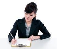 Escritura joven de la empresaria en el sujetapapeles Foto de archivo libre de regalías