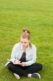 Escritura joven de la mujer del inconformista en su cuaderno en el parque Imagenes de archivo