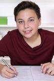 Escritura joven del estudiante en su libro de ejercicio en la escuela Fotos de archivo libres de regalías