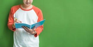 Escritura joven del muchacho del adolescente en el cuaderno azul que se inclina en wal verde Foto de archivo