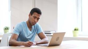 Escritura joven en el papel, papeleo del hombre negro almacen de metraje de vídeo