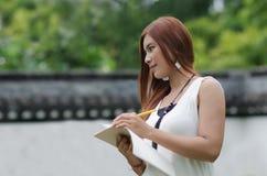 Escritura joven hermosa de la mujer del pelirrojo en un noteboo Foto de archivo libre de regalías