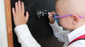 Escritura linda del niño pequeño en la pizarra Niño de la escuela primaria con el bolso Concepto de la educaci?n De nuevo a escue almacen de video