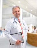 Escritura madura sonriente feliz del doctor en el sujetapapeles imagen de archivo