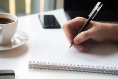 Escritura masculina de la mano en cuaderno con la pluma Endecha plana del negocio: escritorio con el cuaderno, lápiz, vidrios, or imágenes de archivo libres de regalías
