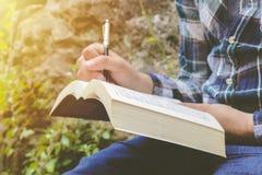 Escritura masculina de la mano en el papel Una mano del hombre es escribe algo Foto de archivo