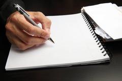 Escritura masculina de la mano en una libreta Foto de archivo