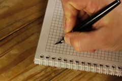 Escritura masculina de la mano usando la pluma en un cuaderno Imágenes de archivo libres de regalías