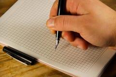 Escritura masculina de la mano usando la pluma en un cuaderno Fotografía de archivo