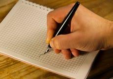 Escritura masculina de la mano usando la pluma en un cuaderno Imagen de archivo