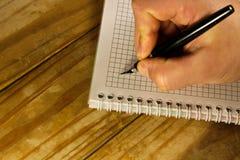 Escritura masculina de la mano usando la pluma en un cuaderno Fotos de archivo libres de regalías