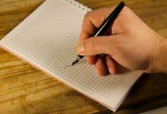 Escritura masculina de la mano usando la pluma en un cuaderno Foto de archivo libre de regalías
