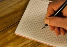 Escritura masculina de la mano usando la pluma en un cuaderno Fotografía de archivo libre de regalías