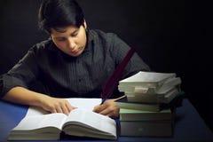 Escritura masculina del adolescente por los libros con la pluma Imagen de archivo
