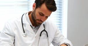 Escritura masculina del doctor en el tablero en el escritorio almacen de video