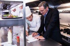Escritura masculina del encargado del restaurante en el tablero mientras que obra recíprocamente al chef foto de archivo libre de regalías