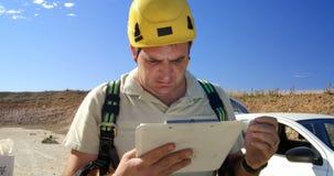 Escritura masculina del ingeniero en el tablero en el parque eólico 4k almacen de video