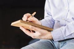 Escritura masculina en libreta Foto de archivo libre de regalías