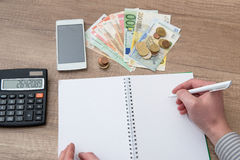 Escritura masculina en una pluma del diario del negocio con la calculadora, dinero euro Fotografía de archivo libre de regalías
