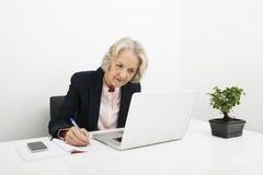 Escritura mayor de la empresaria en libro mientras que usa el ordenador portátil en el escritorio en oficina Fotos de archivo